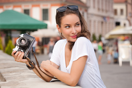 looking away from camera: Gorgeous young brunette woman using analog camera. Stock Photo
