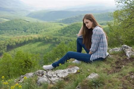 mujeres sentadas: Pensativo hermosa morena joven disfrutando de la vista.