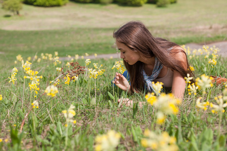 sun drenched: Brunete beauty enjoying relaxation in a sun drenched meadow.
