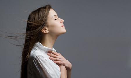 niña pensando: Retrato de una joven belleza morena de ensueño con el pelo azotado por el viento.