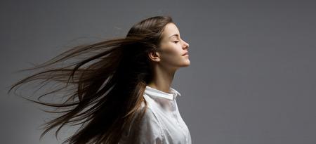 ojos cerrados: Retrato de una joven belleza morena de ensueño con el pelo azotado por el viento.