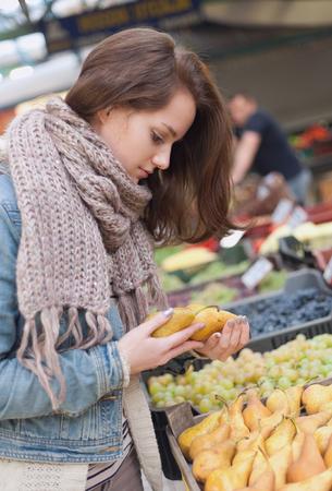 agricultor: Mujer urbana joven de compras para los productos frescos en el mercado de los agricultores.