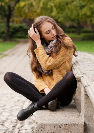 women in jeans: Portrait of a young brunette beauty in autumn clothes.