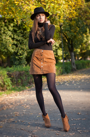 mini: Portrait of a young brunette beauty in autumn clothes.
