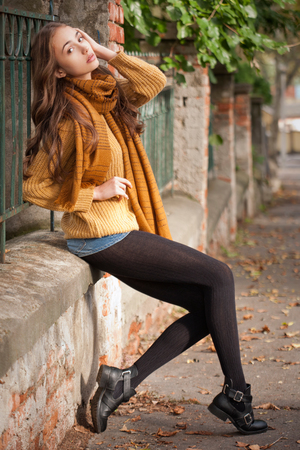 the girl in stockings: Portrait of a young brunette beauty in autumn clothes.