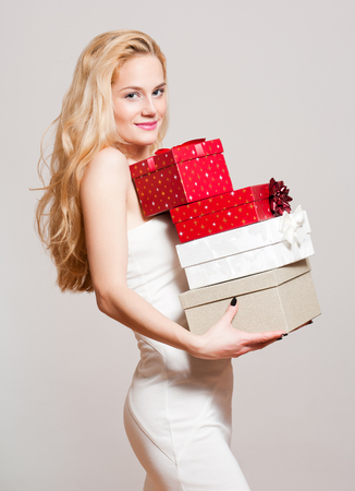 red gift box: Portrait of a gorgeous young blond woman with Christmas gift boxes.