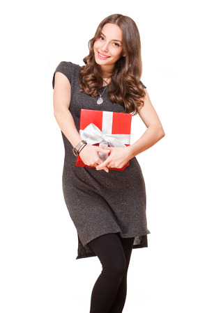 to win: Portrait of a brunette beauty holding red gift box.
