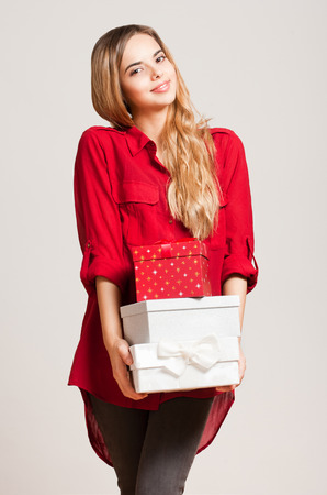Portrait of a gorgeous young woman with decorative gift boxes. photo