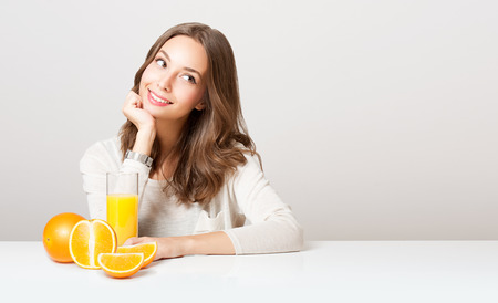 orange juice: Portrait of a healthy young brunette beauty with glass of orange juice and fruit.