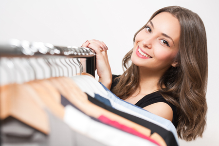 woman closet: Portrait of a gorgeous young brunette woman shopping clothes.