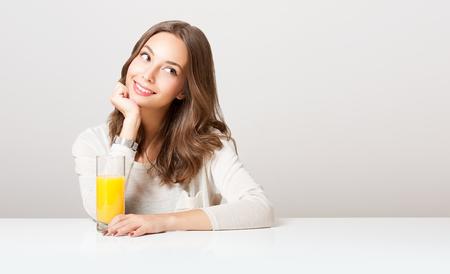 tomando jugo: Retrato de una belleza morena joven y sana con un vaso de jugo de naranja. Foto de archivo