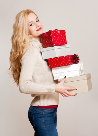 gift boxes: Portrait of a gorgeous young blond woman with Christmas gift boxes.