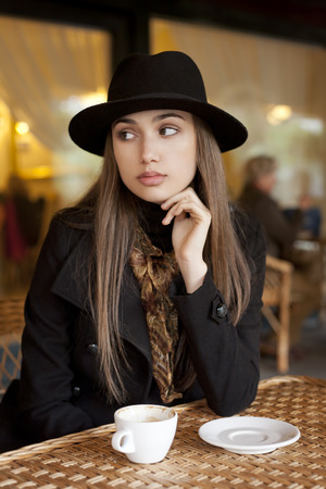 Outdoors portrait of a beautiful young brunette woman having coffee. Stock Photo