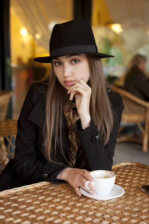 flirt: Outdoors portrait of a beautiful young brunette woman having coffee. Stock Photo