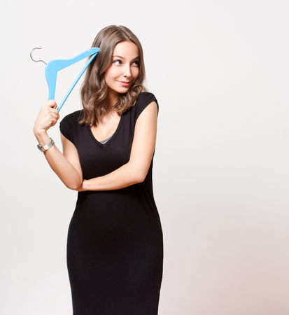 choosing: Portrait of a gorgeous young brunette woman holding clothes hanger. Stock Photo