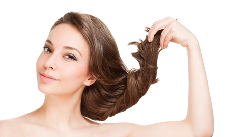 pulling hair: Portrait of a gorgeous young brunette woman with healthy hair.