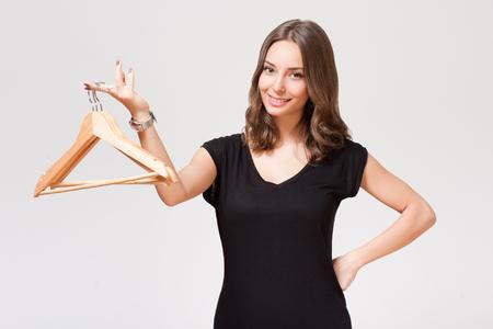woman clothes: Portrait of a gorgeous young brunette woman holding clothes hanger. Stock Photo