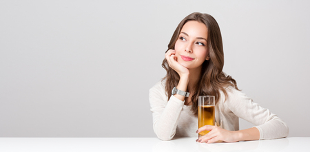 Portrait of a healthy young brunette beauty with glass of apple juice. Archivio Fotografico