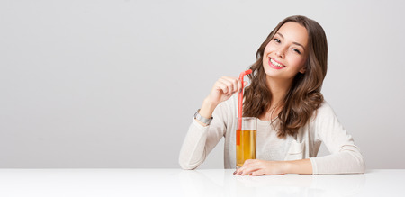 a straw: Studio portrait of a happy young brunette woman with glass of apple juice.