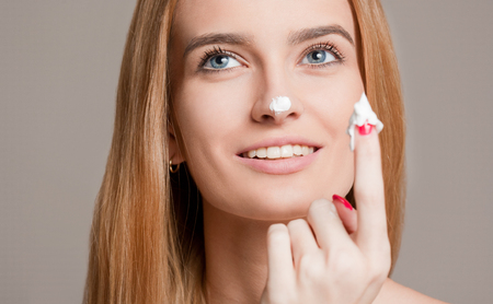 choosing: Portrait of a gorgeous young blond woman using moisturizer.