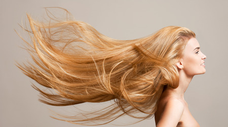 hair treatment: Portrait of a beautiful young blond woman with amazing flowing hair.