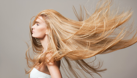 strong wind: Portrait of a blond beauty with beautiful healthy long hair.