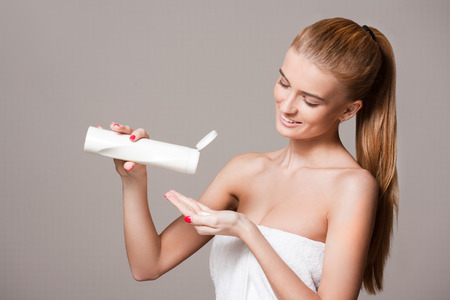 towel: Portrait of a beautiful young blond woman using skin care cosmetics.