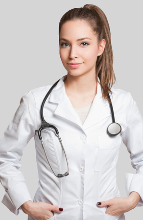 Portrait of an attractive young female doctor in white coat.