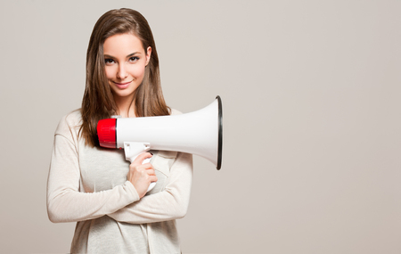 Portrait of a gorgeous young brunette woman holding megaphone.