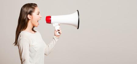 Portrait of a beautiful young brunette woman using loudspeaker.