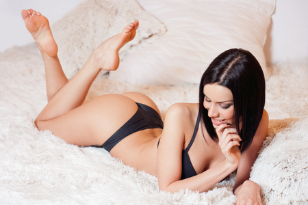 young woman panties: Portrait of a sexy young brunette woman wearing lingerie. Stock Photo