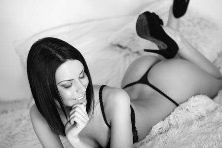 mujer en la cama: Retrato de una mujer sensual morena esbelta joven en ropa interior.