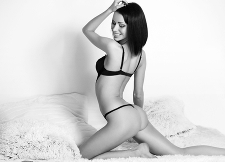kneeling woman: Portrait of a young slender sensual brunette woman in lingerie. Stock Photo