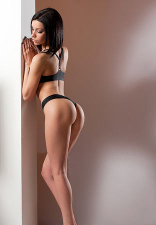 Portrait of a young slender sensual brunette woman in lingerie. Stock Photo
