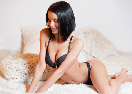 seduction: Portrait of a sexy young brunette woman wearing lingerie. Stock Photo
