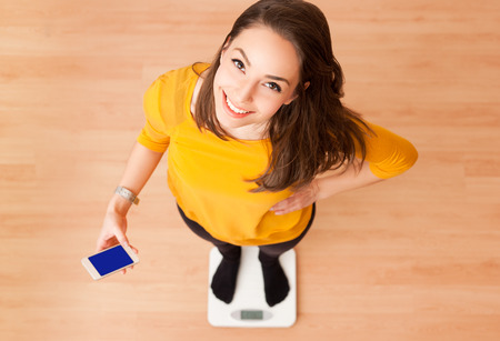 health woman: Portrait of young brunette beauty using household scale. Stock Photo
