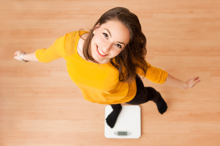 Portrait of young brunette beauty using household scale. Фото со стока