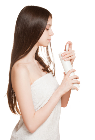 Portrait of a young brunette using body lotion on white background.