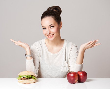 Portrait of a gorgeous young brunette woman showing diet food choices.