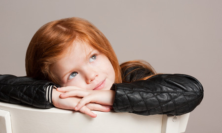 red hair girl: Closeup portrait of a dreamy, thoughtful young child.