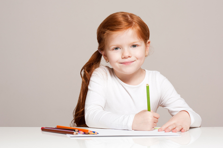 Portrait of beautiful young redhead girl with creative toys.