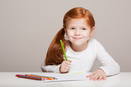 redhead girl: Portrait of beautiful young redhead girl with creative toys. Stock Photo