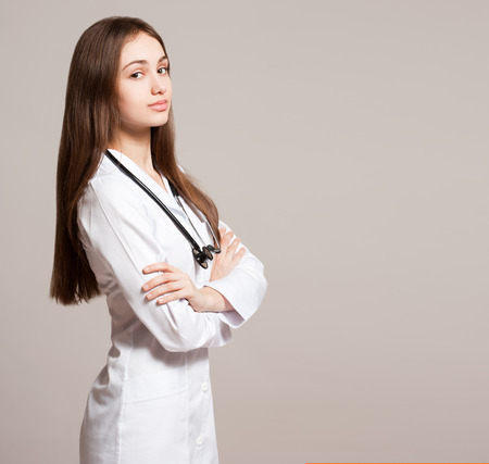 friendly: Portrait of an attractive young female doctor in white coat.
