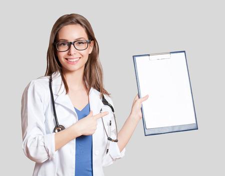 bata blanca: Retrato de una mujer médico joven y atractiva en la capa blanca.