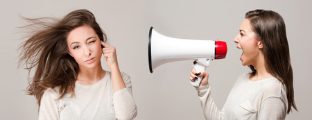 Beautiful young brunette with loudspeaker, approach to self concept. Stock Photo