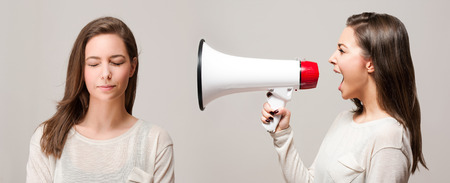Beautiful young brunette with loudspeaker, approach to self concept.