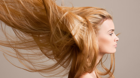groomed: Portrait of a beautiful young blond woman with amazing flowing hair.