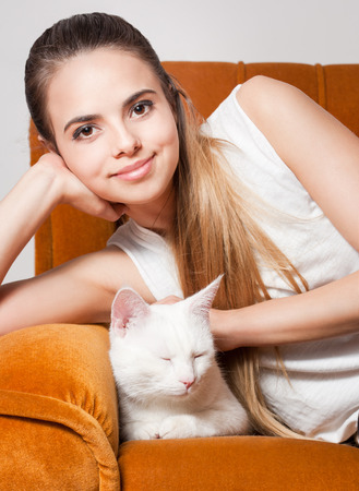 Portrait of a beautiful young brunette woman having fun with cat. photo