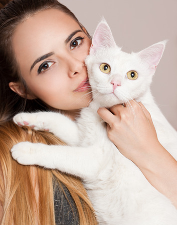 Portrait of young brunette beauty holding gorgeous white cat. photo