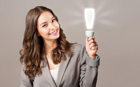Creative ideas concept, beautiful businesswoman holding glowing symbol.